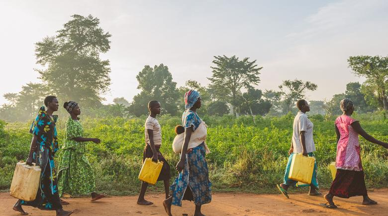 Women carry containers of water