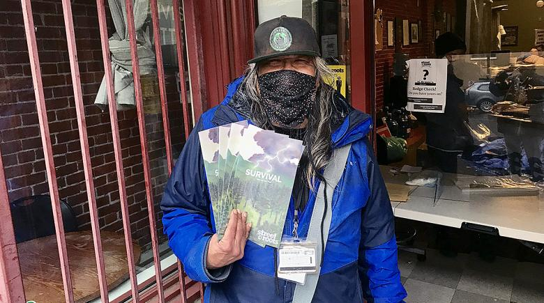 Daniel Cox holds several copies of the Street Roots zine