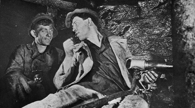 Historical photo shows Alexei Stakhanov with a mining drill, talking to another miner