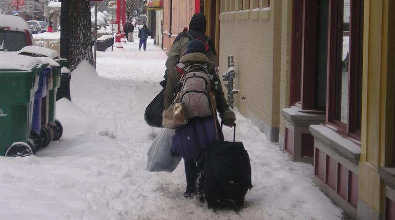 People carry their possessions through the snow in Old Town Portland