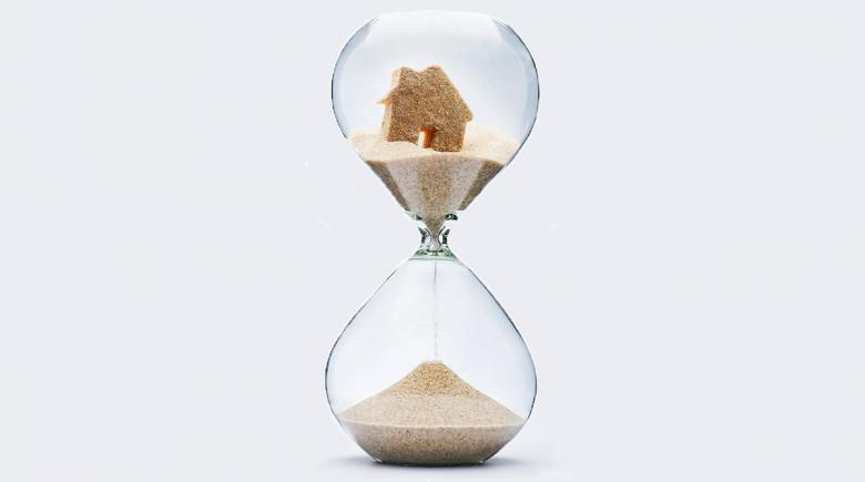 Illustration of sand falling in an hourglass that contains a house
