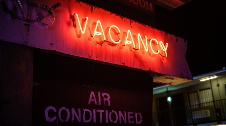A vacancy sign shines bright outside of a motel