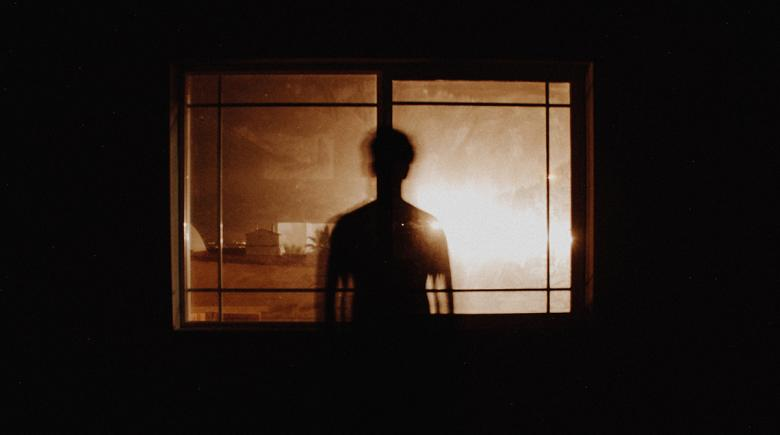 Silhouette of a person in front of a window