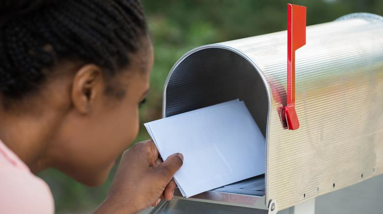 A student puts letters into a mailbox