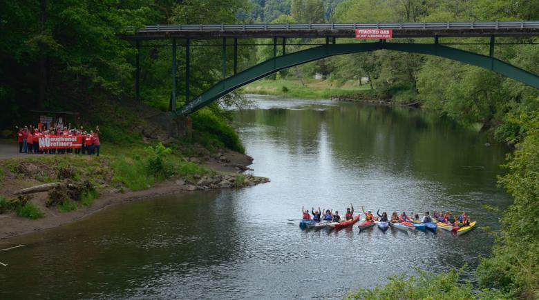 """A group of people holds a """"No Methanol"""" sign beside the river while others float in kayaks in the river"""