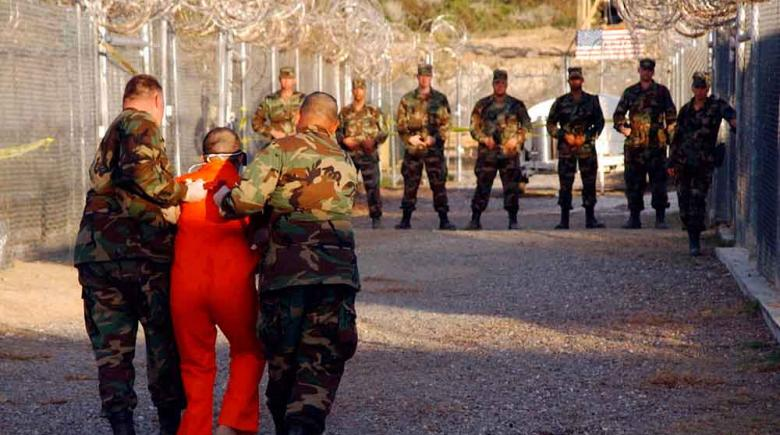 A detainee is escorted to his cell at Guantanamo Bay