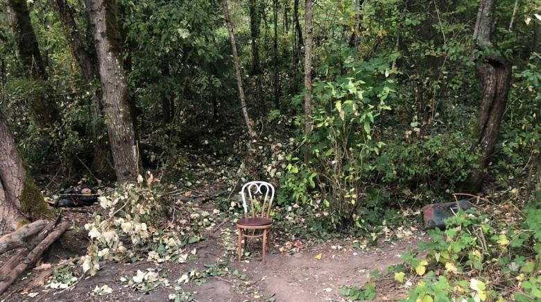 A lone chair sits on a path in Forest Park. Evidence of people living in the park is strewn about.