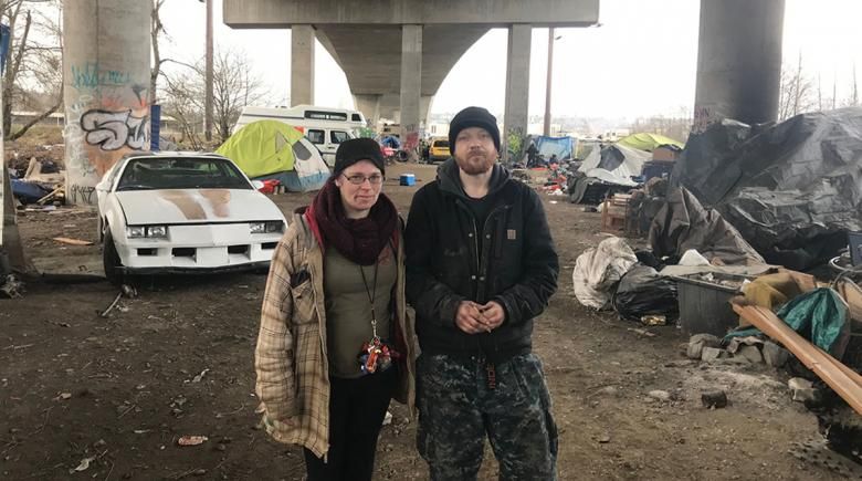 Two houseless people stand in front of an encampment under a freeway overpass in Seattle.