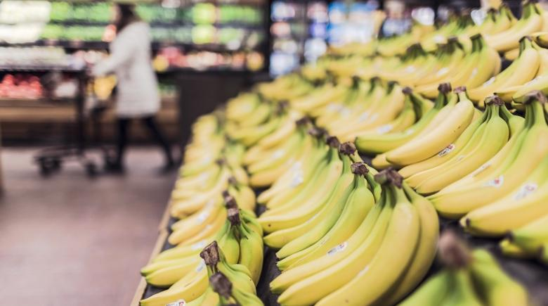 A person shops in the produce aisle of a grocery store