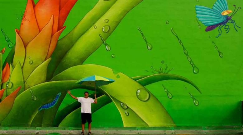 This Miami mural was designed by artists Waone, pictured, and AEC — an art duo known as Interesni Kazki.