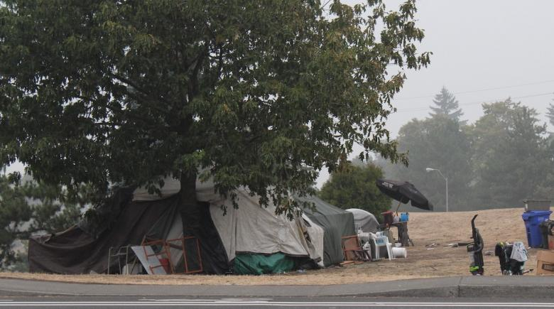 A homeless encampment along North Rosa Parks Way is pictured amid wildfire smoke.