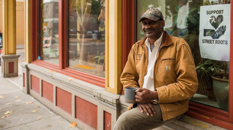 Photo of Gary Barker sitting outside the Street Roots office with a cup of coffee in his hand