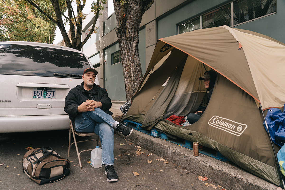 Mike sits in a chair outside a tent with his friend in it