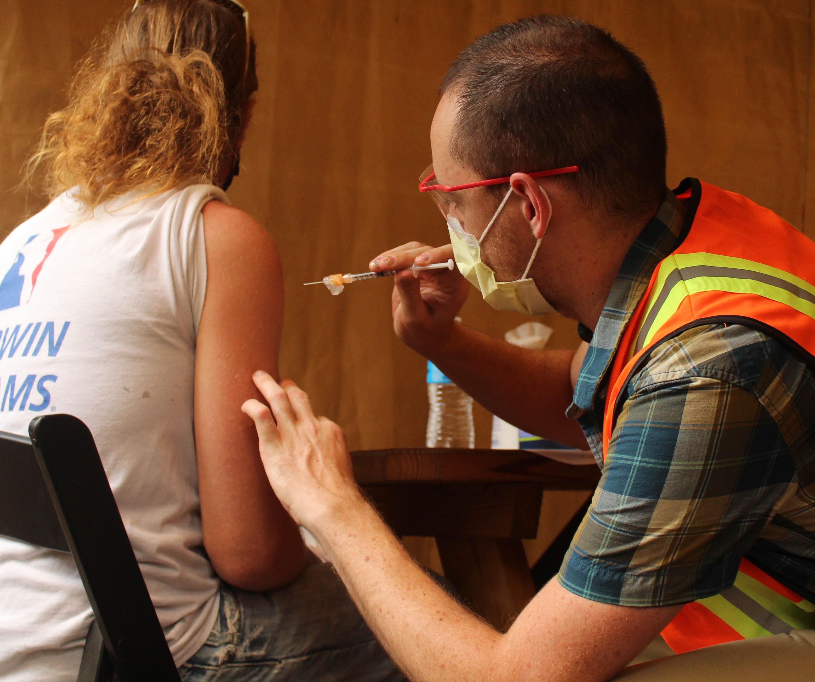 An OHSU technician is preparing to vaccinate Don Atkinson.
